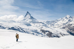 Un uomo che ondeggia la sua mano che sta sulla neve nei precedenti del Cervino Immagini Stock