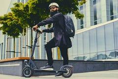 Un uomo che posa sul motorino elettrico fotografia stock libera da diritti