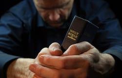 Un uomo che prega tenendo una bibbia. Fotografie Stock