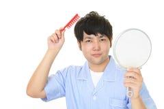 Un uomo che prende cura dei suoi capelli Immagini Stock Libere da Diritti