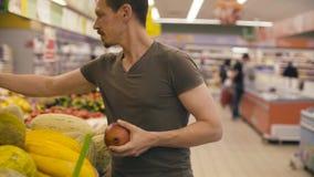Un uomo che prende granato in un supermercato stock footage