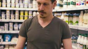 Un uomo che prende latte in un supermercato video d archivio