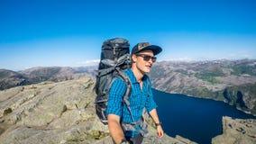 Un uomo che prende un selfie e che fa un'escursione lungo un fiordo in Norvegia È sul a Preikestolen immagine stock libera da diritti