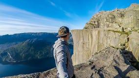 Un uomo che prende un selfie e che fa un'escursione lungo un fiordo in Norvegia fotografia stock libera da diritti