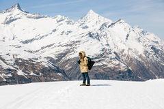 Un uomo che prende una foto con la macchina da presa d'annata sulla neve nei precedenti della montagna della neve Fotografia Stock Libera da Diritti