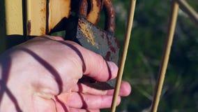 Un uomo che prova ad aprire la serratura arrugginita arrugginita della serratura di porta, stock footage