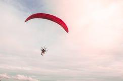 Un uomo che sale nel cielo con l'avventura estrema di sport di paramotor nel tempo di giorno di estate con un chiaro fondo del ci Fotografia Stock