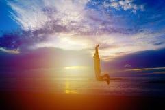 Un uomo che salta sulla spiaggia al tramonto con luce calda Immagini Stock Libere da Diritti