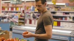 Un uomo che sceglie le verdure in un supermercato stock footage