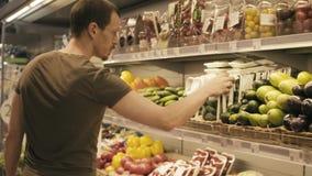 Un uomo che sceglie le verdure in un supermercato video d archivio