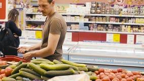 Un uomo che sceglie le verdure in un supermercato archivi video