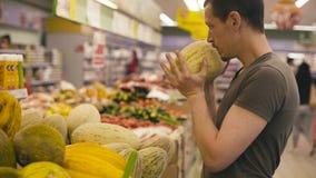 Un uomo che sceglie melone in un supermercato archivi video