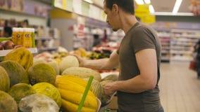 Un uomo che sceglie melone in un supermercato video d archivio