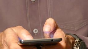 Un uomo che scrive su uno smartphone del touch screen video d archivio