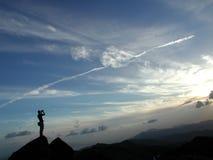 Un uomo che si leva in piedi alla parte superiore della montagna Fotografia Stock