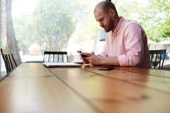 Un uomo che si siede ad una grande tavola di legno in suo telefono della mano Immagini Stock Libere da Diritti