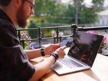 Un uomo che si siede ad una tavola di legno sta tenendo un telefono Sullo scrittorio è un computer portatile Fotografia Stock