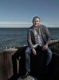 Un uomo che si siede su una parete dal mare Fotografia Stock Libera da Diritti