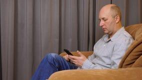 Un uomo che si siede su una sedia che parla con telefono L'uomo sta tenendo il telefono in sua mano e sta parlando sulla viva voc archivi video