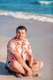 Un uomo che si siede sulla spiaggia fotografia stock