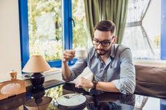 Un uomo che si siede in un caffè e che esamina il suoi orologio e caffè della bevanda Fotografia Stock Libera da Diritti