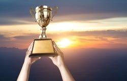 un uomo che sostiene una tazza del trofeo dell'oro con il fondo co del cielo di tramonto Immagine Stock