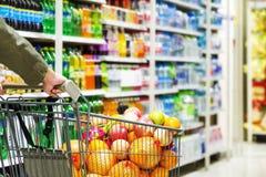 Un uomo che spinge un carretto in pieno di frutta sugli scaffali di negozio Immagine Stock Libera da Diritti