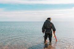 Un uomo che sta knee-deep nell'acqua che cerca i metalli preziosi con un metal detector Mare e cielo sui precedenti immagine stock