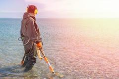 Un uomo che sta knee-deep nell'acqua che cerca i metalli preziosi con un metal detector Mare e cielo sui precedenti Luce da fotografia stock