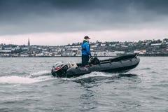 Un uomo che sta su una barca di Cork Harbour Boat Hire, una società per la locazione delle barche dell'azionamento di auto a gran fotografie stock libere da diritti
