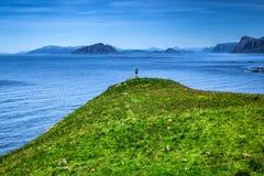 Un uomo che sta sul picco della montagna che trascura costa e l'Oceano Atlantico norvegesi immagini stock