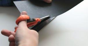 Un uomo che taglia un foglio di carta con un paio di forbici archivi video
