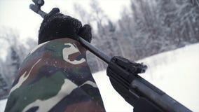Un uomo che tende una pistola della pallina verso un obiettivo, praticante il suo scopo nell'inverno clip Il tiratore in cammuffa fotografia stock