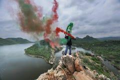 Un uomo che tiene i bastoni di colore in sua mano su un paesaggio v immagini stock libere da diritti