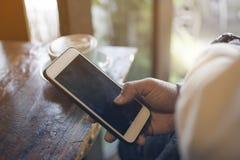 Un uomo che tiene lo Smart Phone nero dello schermo con caffè caldo vago al caffè nella stagione invernale immagine stock