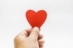 Un uomo che tiene una forma rossa del cuore in sue mani Fotografia Stock Libera da Diritti