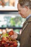 Un uomo che tiene una mela Immagini Stock
