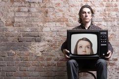 Un uomo che tiene una retro TV Immagine Stock
