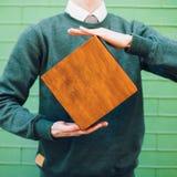 Un uomo che tiene una scatola di legno immagini stock