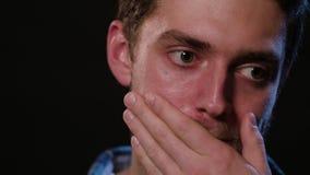Un uomo che tocca le sue labbra contro un fondo nero fotografie stock libere da diritti