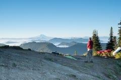 Un uomo che trascura le montagne al suo campeggio con il gea di campeggio Fotografia Stock Libera da Diritti