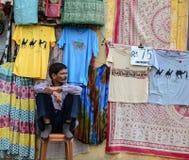 Un uomo che vende i vestiti sulla via a Jaipur, India Fotografia Stock