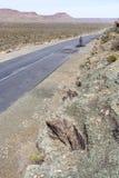 Un uomo cicla su una strada aperta e vuota di karoo Immagini Stock