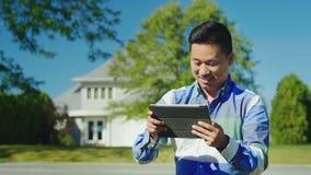 Un uomo cinese allegro utilizza una compressa vicino alla sua casa fotografie stock