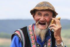 Un uomo cinese anziano si è vestito con l'abbigliamento tradizionale che fuma mentre godeva del panorama di DongChuan nella provi Fotografia Stock Libera da Diritti
