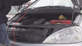 Un uomo collega i cavi ad alta tensione da un'automobile erogatrice per caricare un motore di automobile con una batteria scarica stock footage