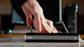 Un uomo collega il cavo di Ethernet al porto PALLIDO del router di WiFi video d archivio