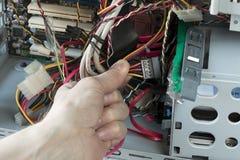 Un uomo collega il HDD al desktop pc Riparazione di attrezzatura del tecnico fotografie stock