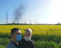 Un uomo con un bambino in sue mani nelle maschere mediche sui precedenti della pianta Il concetto di inquinamento ambientale, eco immagine stock libera da diritti