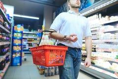 Un uomo con un cestino della spesa di rosso passeggia intorno al supermercato Un uomo compra le merci in un supermercato fotografie stock